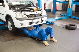 36351703 - mechanic lying and working under car at the repair garage